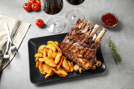 Delicious grilled ribs served on light grey table