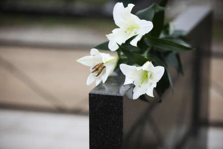 White lilies on black granite tombstone outdoors. Funeral ceremony 스톡 콘텐츠