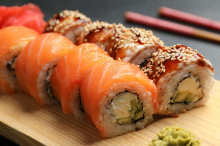 Delicious sushi rolls on wooden tray, closeup