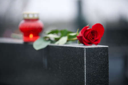 Red rose and candle on black granite tombstone outdoors. Funeral ceremony