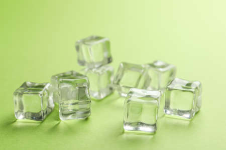 Crystal clear ice cubes on light green background
