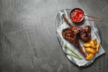 Delicious grilled ribs served on grey table, top view. Space for text
