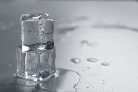 Crystal clear ice cubes with water drops on grey table, closeup. Space for text