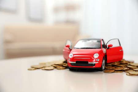 Modelo de automóvil en miniatura y dinero en la mesa en el interior, espacio para texto. Compra de coches Foto de archivo