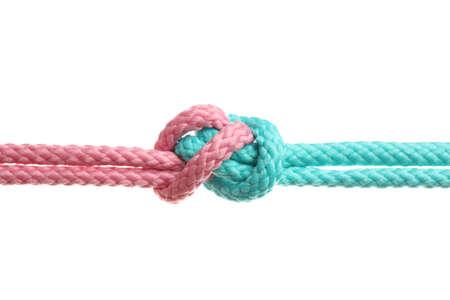 Bunte Seile zusammengebunden mit Knoten, isoliert auf weiss. Einheitskonzept