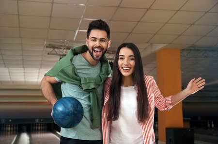 Happy young couple with ball in bowling club Stock Photo