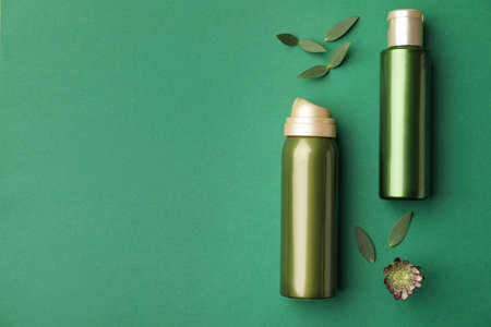 Flat lay composition with cosmetic products on green background. Space for text