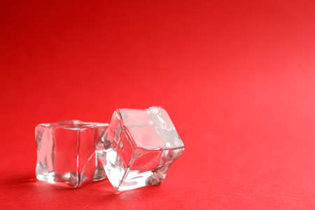 Crystal clear ice cubes on red background. Space for text