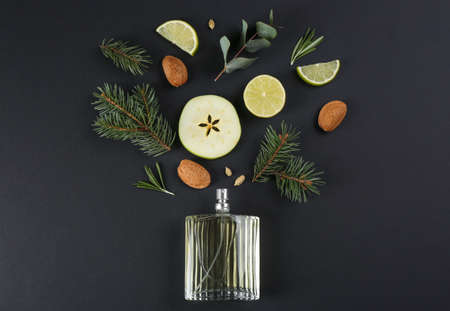 Flat lay composition with bottle of perfume on black background
