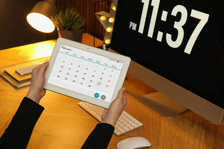 Woman using tablet with calendar app at workplace, closeup