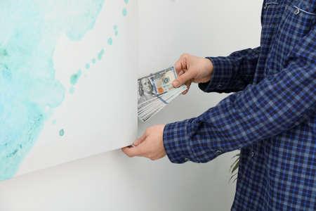 屋内で絵を描く後ろにドル紙幣を隠している男、クローズアップ。お金の節約