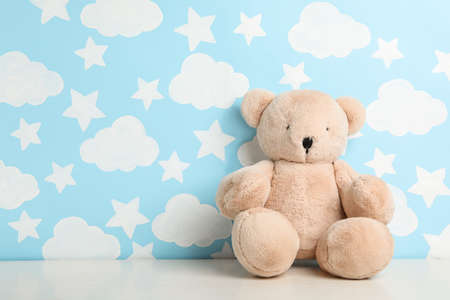 Teddy bear on white table near wall with painted blue sky, space for text. Baby room interior