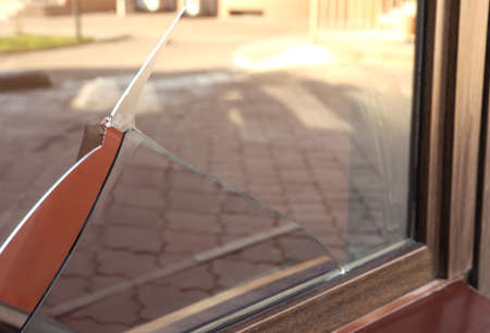 Broken window with sharp smithereens outdoors. Requiring repair