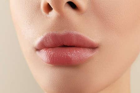 Woman with beautiful full lips on beige background, closeup Фото со стока