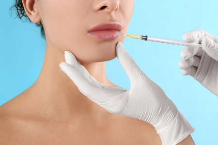 Woman getting lip injection on light blue background, closeup