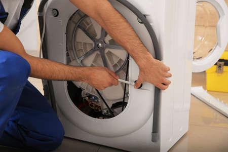 Professional plumber repairing broken washing machine, closeup