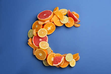 Letter C made with citrus fruits on blue background as vitamin representation, flat lay