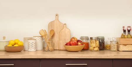 Wooden countertop with dishware and products near white wall. Kitchen interior idea