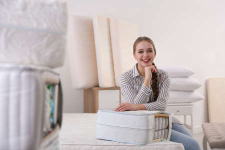 Young woman with section of mattress in furniture store. Space for text