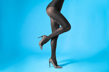 Woman wearing black tights and stylish shoes on blue background, closeup of legs