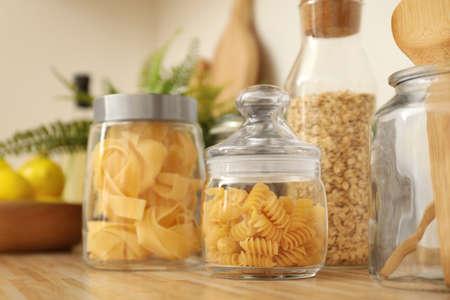 Pots avec des produits sur le comptoir de cuisine en bois