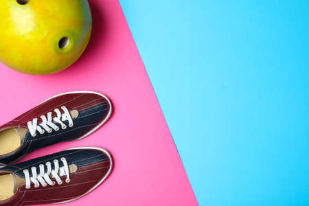 Bowling ball and shoes on color background, flat lay. Space for text
