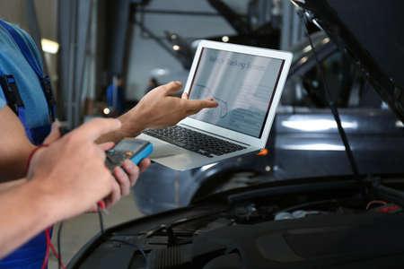 Mechanics with laptop doing car diagnostic at automobile repair shop, closeup Stock Photo
