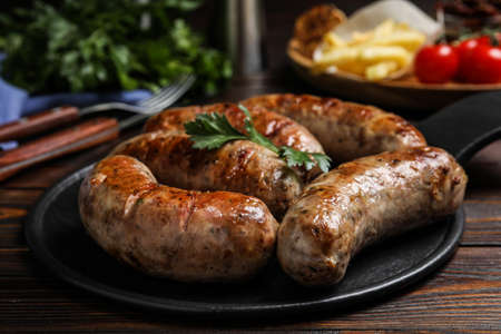 Delicious fresh grilled sausages on wooden table Stock Photo
