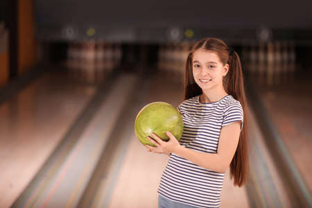 Preteen girl with ball in bowling club. Space for text