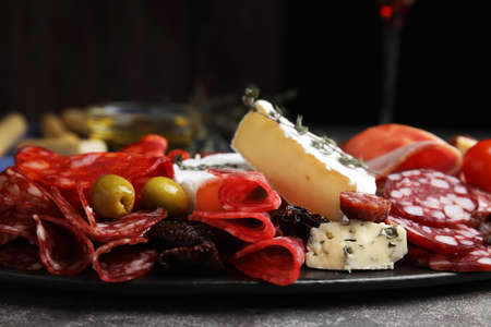 Tasty salami and other delicacies served on grey table, closeup