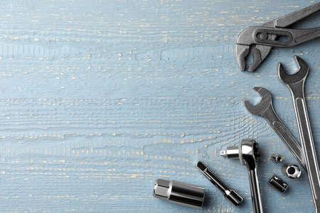 Nowoczesne narzędzia mechanika samochodowego na szarym drewnianym stole, płasko leżał. Miejsce na tekst