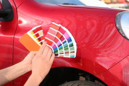 Mujer con muestras de paleta eligiendo el color para pintar el coche, primer plano Foto de archivo