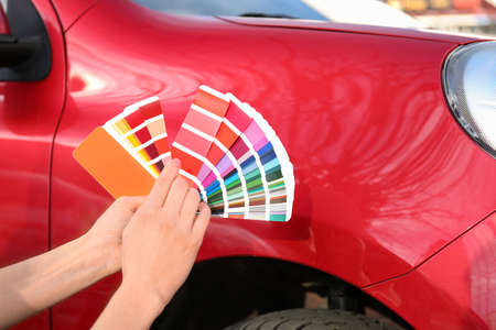 Woman with palette samples choosing color for painting car, closeup Banque d'images