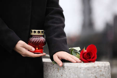 Woman holding candle near grey granite tombstone outdoors, closeup. Funeral ceremony