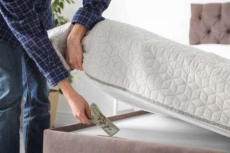 Homme cachant des billets en dollars sous le matelas dans la chambre, gros plan. Économies d'argent