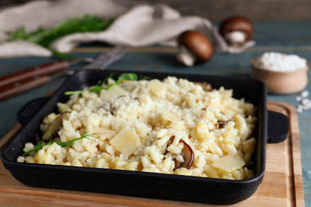 Delicious risotto with cheese and mushrooms on wooden board, closeup Banco de Imagens
