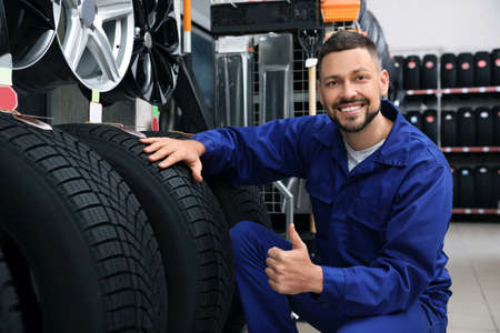 Male mechanic with car tires in auto store