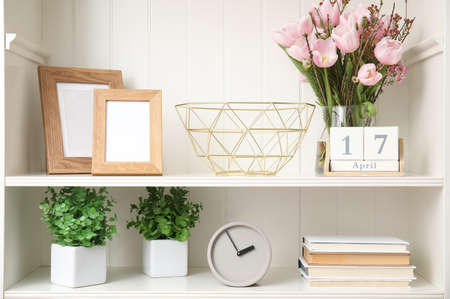 White shelving unit with plants and different decorative stuff Stock Photo