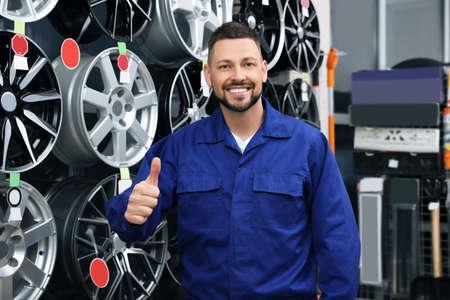 Male mechanic near alloy wheels in auto store Stock fotó