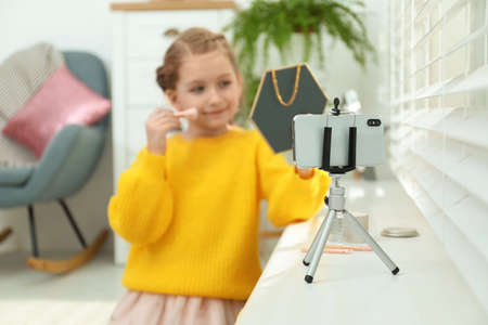 Cute little blogger with cosmetics recording video at home, focus on phone 스톡 콘텐츠