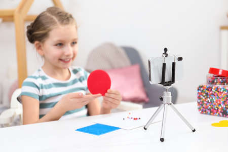 Cute little blogger with handcrafting recording video at home, focus on phone 스톡 콘텐츠