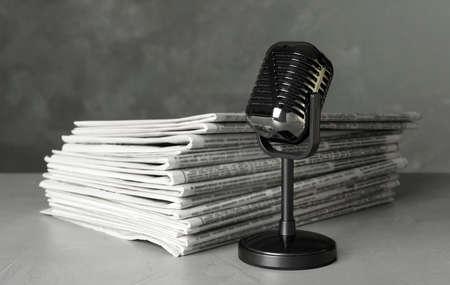 Giornali e microfono vintage su tavolo in pietra grigio chiaro. Il lavoro del giornalista