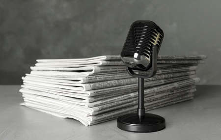 Newspapers and vintage microphone on light grey stone table. Journalist's work
