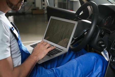 Mécanicien avec ordinateur portable faisant un diagnostic de voiture dans un atelier de réparation automobile, gros plan
