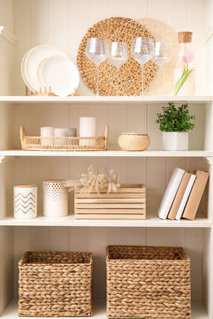 White shelving unit with dishware and different decorative stuff Stock Photo
