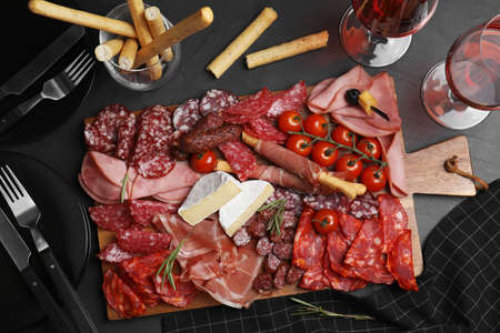 Tasty ham with other delicacies served on black table, flat lay Фото со стока