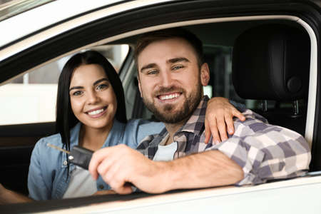 Happy couple with car key sitting in modern auto at dealership