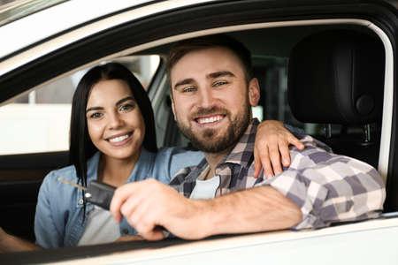 Pareja feliz con llave de coche sentado en auto moderno en concesionario