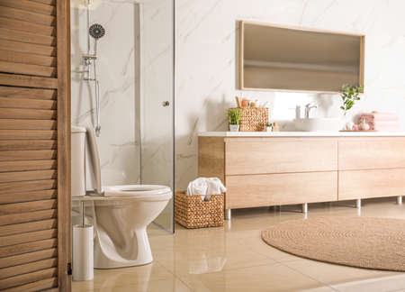 Elegant modern bathroom with wooden cabinet near marble wall Stock Photo