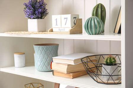 Estantería blanca con libros y diferentes elementos decorativos.